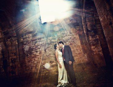 2 mariés s'embrassant dans une vieille abbaye en ruines, traversée par un rayon de soleil
