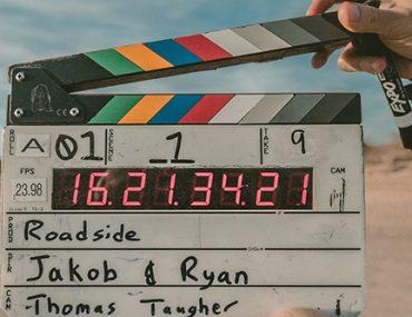 Photo présentant un clap de cinéma avec pour fond un décor désertique digne de Mad Max