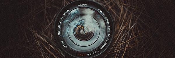 Lentille frontale d'un objectif photo CANON laissant apparaitre les caractéristiques principales de celui-ci