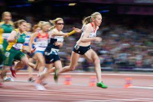 Des sprinteuses s'échangent le témoin et sont floutées à 1/50s, sauf la première dont le visage et le torse restent nets