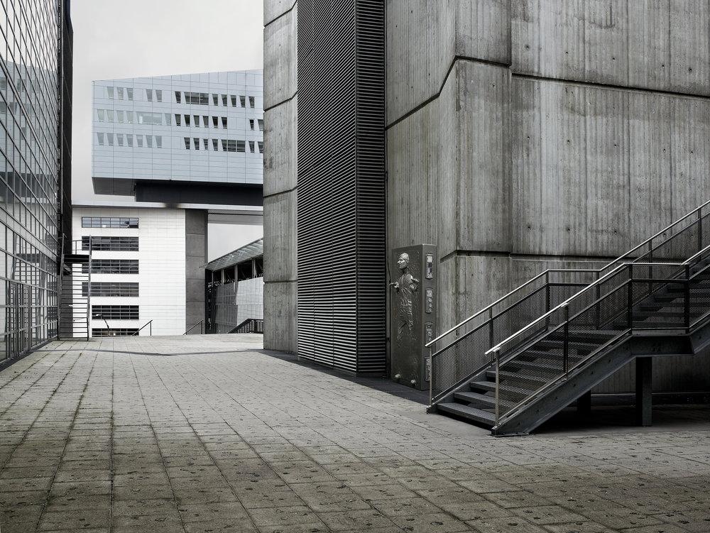 Extrait de la série Dark Lens Origins de Cédric Delsaux. Lille 2007, vue d'une banlieue grise, Han Solo pris dans la carbonise intégré dans le paysage