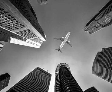 Photographie d'un avion au milieu des tours en noir et blanc par Sasin Tipchai