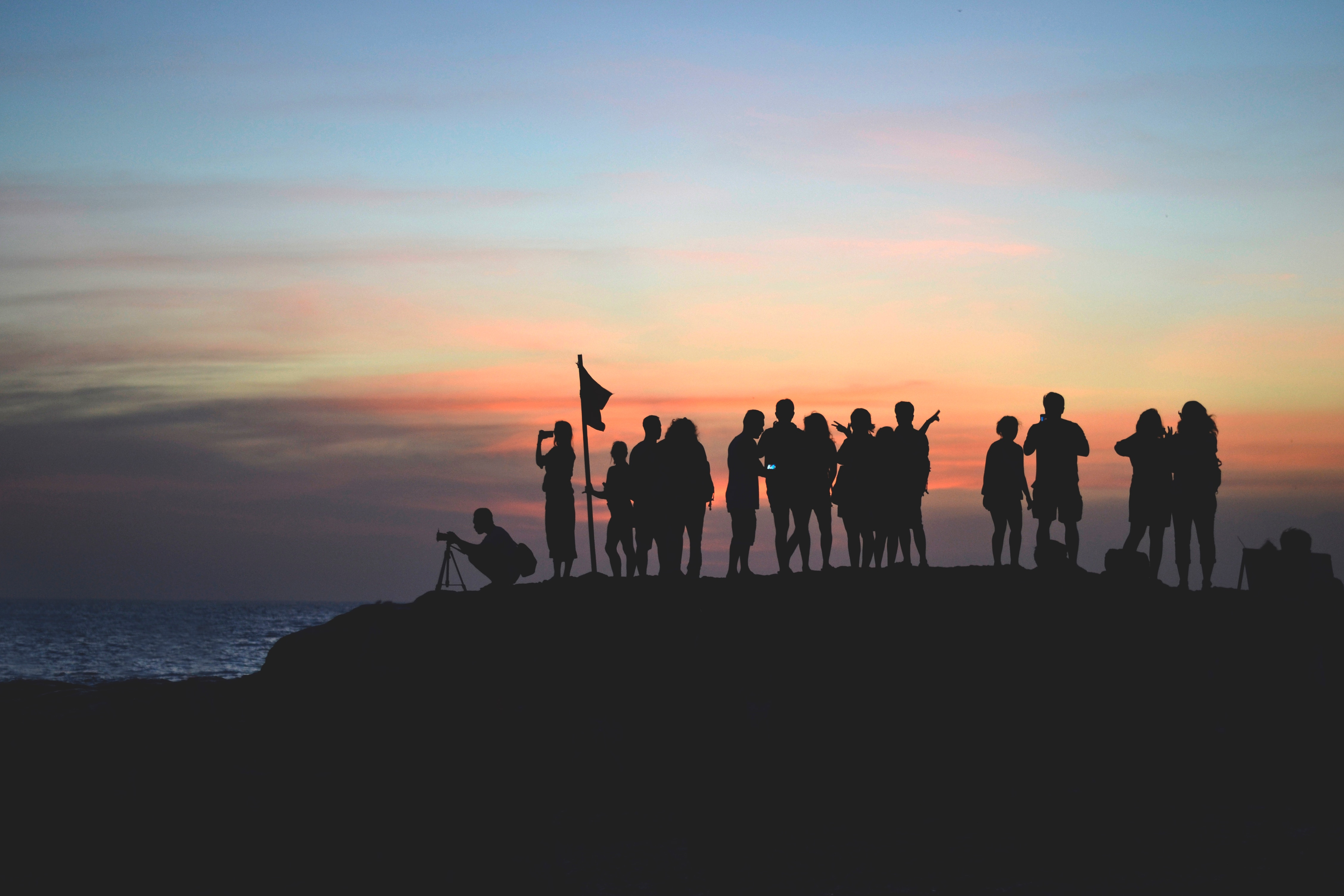 Photo présentant un groupe de personnes en ombres près de la mer