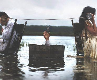Un homme et une femme dont on ne voit pas les visages sont assis, dos à dos, sur des chaises en bois au coeur d'un marais. Ils sont reliés par un fil accroché à deux boites de conserve qu'ils tiennent à leur oreille. Un milieu, un tonneau de bois, duquel surgit un bras tenant un ciseau ouvert, prêt à le couper.