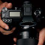 Photo présentant des mains tenant le Panasonic S1 en kit avec l'objectif 24-105, le tout sur un fond noir