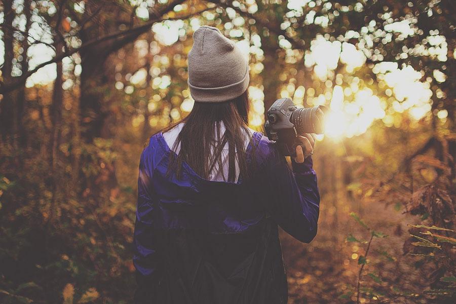 image d'une jeune femme en recherche d'inspiration photographique au milieu d'une forêt