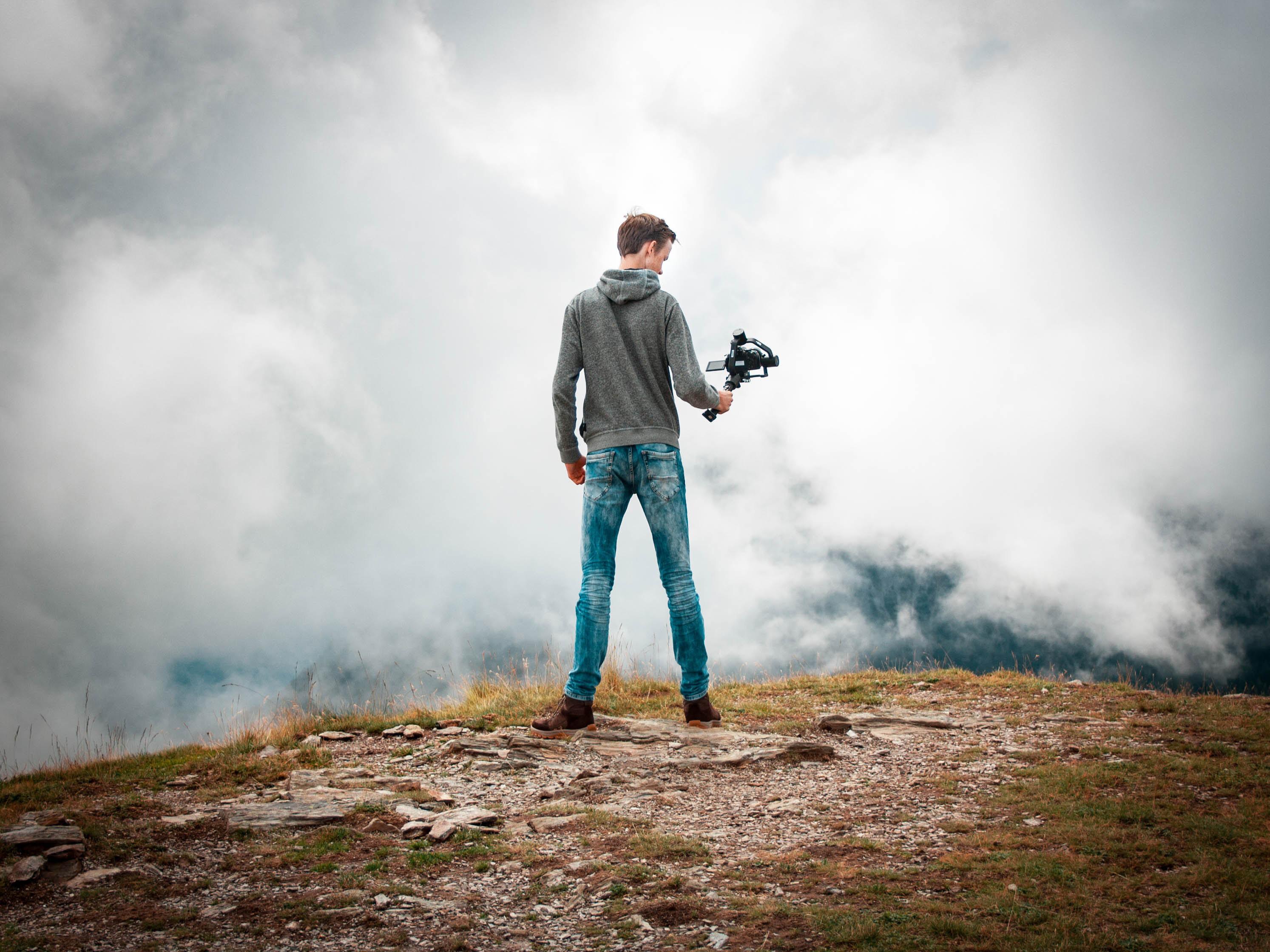 Photo présentant un homme, stabilisateur à la main, en haut d'une colline