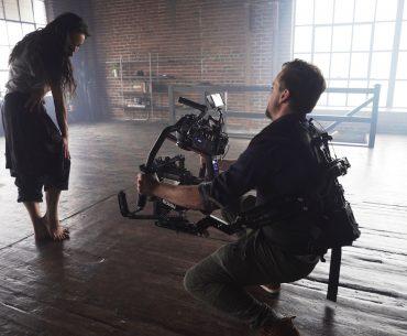 Photo montrant un cadreur stabilisateur à la main dans un entrepôt où se tient une femme debout